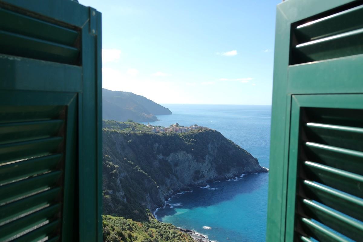 les volets s'ouvrent sur une vue de corniglia aux cinque terre en italie